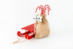 Sledge and candy canes in jute sack with jingle bells and Christmas star isolated on white with copy space.