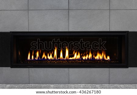 Sleek modern gas fireplace with gray tile surround and black glass media reflecting the flames #436267180