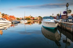Sleek power boats are anchored in the tranquil morning waters of Annapolis Harbor, also known as