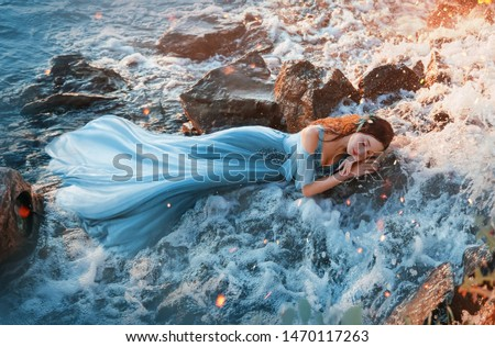 Photo of  sleep beauty charming sea princess resting on wet stones, girl in blue long tender dress lies in cold water waterfall hands under head red hair, young woman river nymph mermaid cute face. rays sun