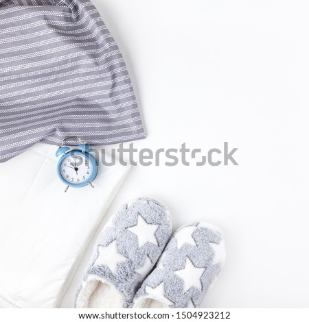 Sleep. Soft fluffy slippers and blue alarm clock isolated on white background. Creative conceptual top view flat lay in minimal style. Rest, good night, insomnia, relaxation, tired, hygge concept
