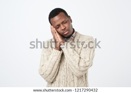 Sleep time. Tired african young man standing with closed eyes leaning on palms as pillow pretending sleeping being exhausted. Studio shoot
