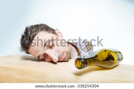 Sleeping alcoholic. Drunk man with empty wine bottle, sleeping on the table. Сток-фото ©