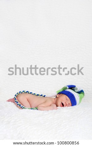 Sleeping and smiling newborn wearing a knitted winter hat
