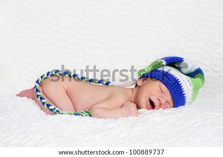 Sleeping and smiling newborn wearing knitted hat
