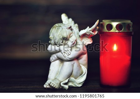 Sleeping angel and All Saints Day burning candle