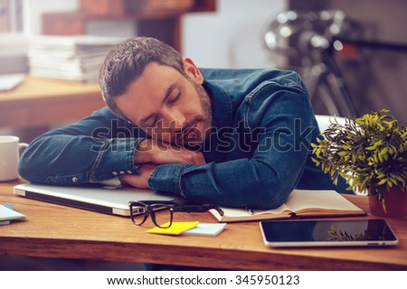 Sleeping at working place. Young man leaning his head on desk and keeping eyes closed while sitting at his working place