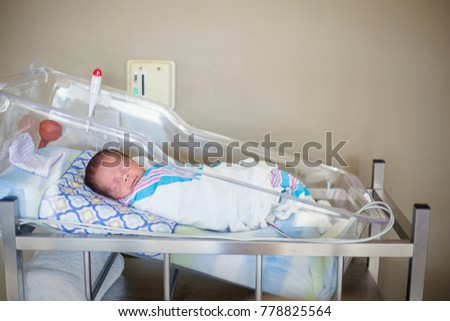 Sleeping baby boy resting in a hospital crib in a hospital delivery room. The ethnically diverse child is peaceful and content in his bed #778825564