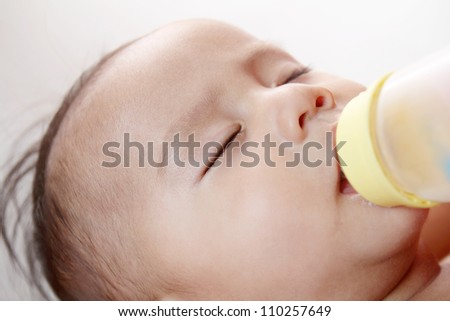 Sleeping baby boy while on bottle feeding.Close up.
