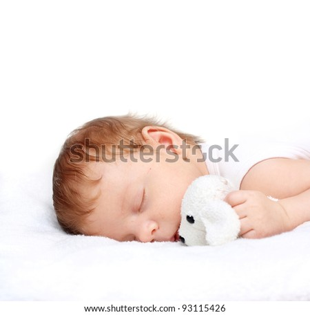 Sleeping Baby Boy with toy on a White Blanket