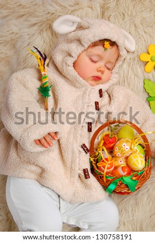 sleeping baby girl as easter sheep holding wicker basket with colorful eggs