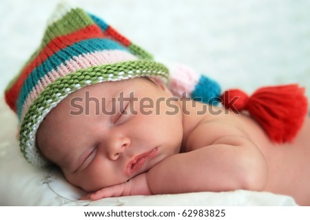 stock photo : Sleeping baby girl wearing a striped hat