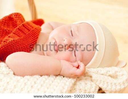 sleeping baby in a wicker basket
