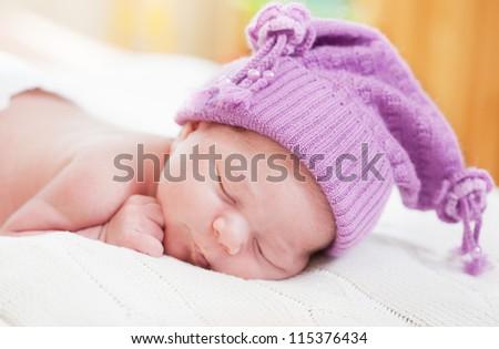 sleeping baby in an amusing violet hat