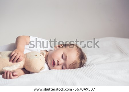 Sleeping baby in bed, holding a teddy bear.