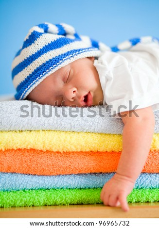 Sleeping baby on colorful towels stack