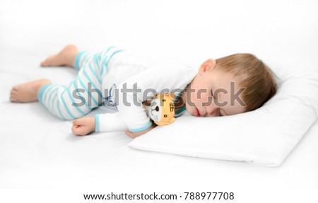 Sleeping baby on white background. Toddler boy in pijama sleeps on white pillow under blanket