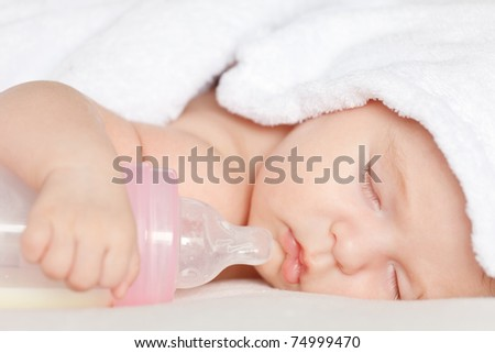 Sleeping baby with bottle - stock photo