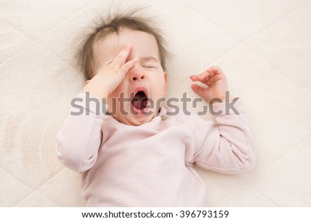Sleeping beautiful and yawning baby toddler on the bed. Portrait