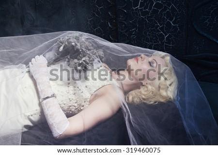 Stock Photo Sleeping Beauty. Beautiful lifeless bride in white dress lying on the shore in a tomb. Dark mystery scene. Low key