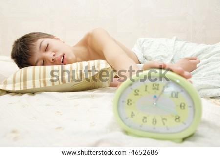 Sleeping boy and alarm clock in the bedroom Foto stock ©
