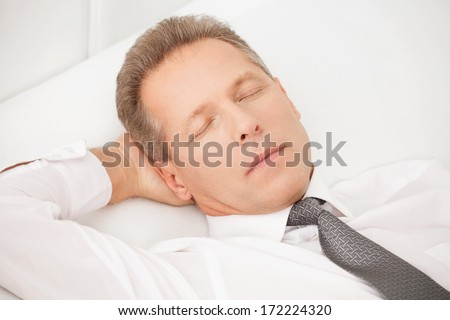 Sleeping businessman. Tired grey hair man in shirt and tie lying on bed and keeping eyes closed
