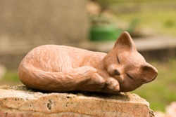 Sleeping cat statue on a memorial stone