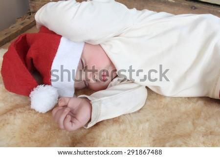 Sleeping christmas baby on a sheep skin rug wearing