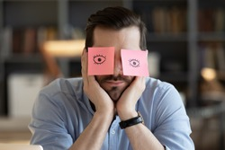 Sleeping clerk hides eyes with sticky notes, open eyes drawn on adhesive papers, he wants to sleep at workplace due lack of energy, chronic fatigue, not inspired, no motivation office employee concept