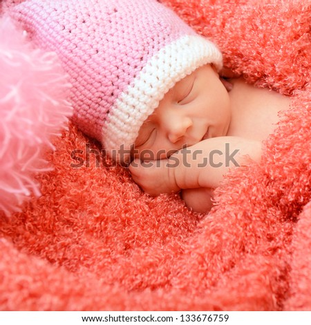 sleeping cute baby funny pink hat in soft fabric and smiling in sweet dreams, beautiful kid\'s face closeup