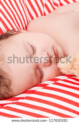 sleeping cute little baby on red and white stripes pillow with teddy bear