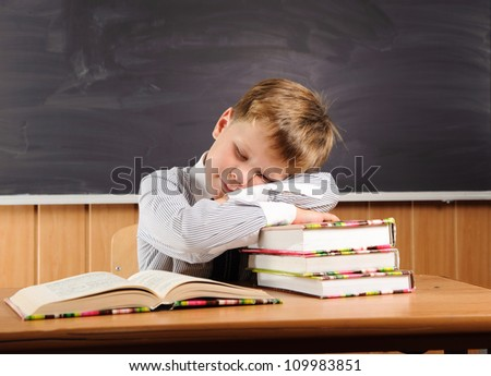 Sleeping  elementary aged boy sitting at the desk with books