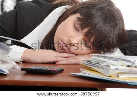 Sleeping female filling out tax forms while sitting at her desk. Isolated