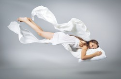 Sleeping girl. Flying in a dream. White linen flying through the air. Light grey background