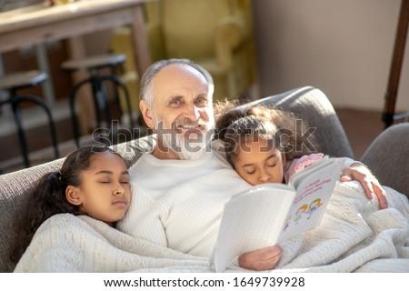 Sleeping girls. Two girls sleeping on the sofa hugging their granddad.