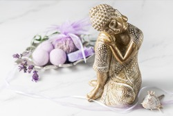 Sleeping  golden Buddha statuette and wellness set with lavender flowers on white marble background. Spa or meditation concept