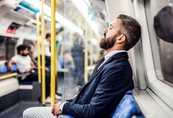 Sleeping hipster businessman inside the subway in the city, travelling to work.