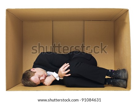 Sleeping in a cardboard box isolated on white background