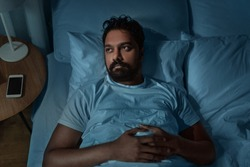 sleeping, insomnia and people concept - speelpess indian man lying in bed at home at night