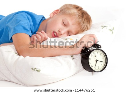 Sleeping kid with alarm clock in front