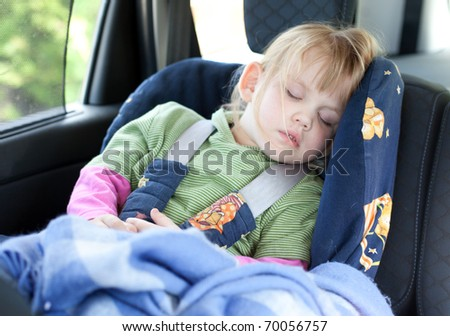 sleeping little, blond hair girl in car seat
