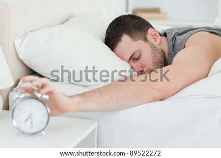 Sleeping man being awakened by an alarm clock in his bedroom