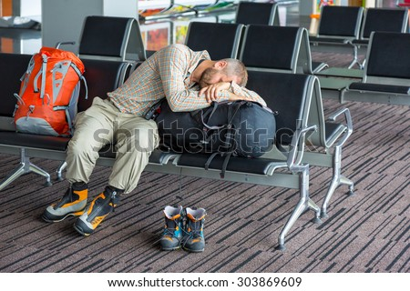 Sleeping man inside transport terminal.\ Man couching on his luggage waiting for train departure sport smart casual relaxed dress code soft shirt and pants heavy winter boots interior background