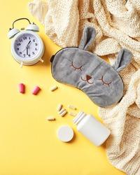 Sleeping mask, alarm clock, earplugs and pills. Healthy night sleep creative concept. Flat lay, top view. Good night, sleep hygiene, insomnia