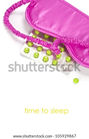sleeping mask and pills over white
