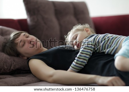 Sleeping mother and toddler on a sofa at home