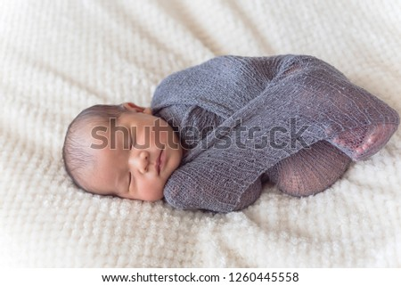 Sleeping newborn Asian baby boy swaddled in purple knitted mohair wrap
