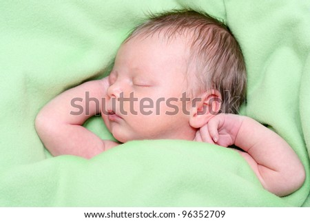 Sleeping Newborn Baby Boy in a Green Blanket