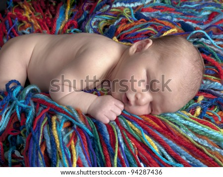 Sleeping newborn baby boy one week old he is laying on a blanket of multicolored yarn. - stock photo