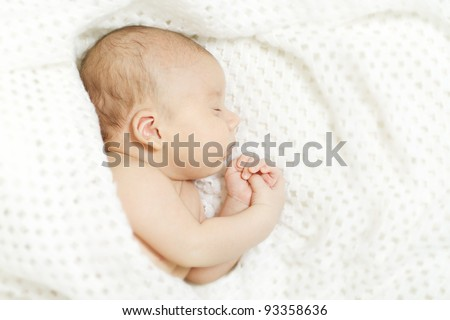 Sleeping newborn baby covered with white woolen blanket.